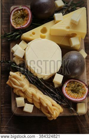 Cheese Platter With Herbs.soft And Hard Cheeses Set, Passionfruit Cut, Rosemary On Dark And Light Bo