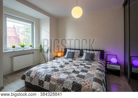 View Of King-size Bed And Bedsides With Round Lamps In Modern Bedroom. Interior In Light Tones.