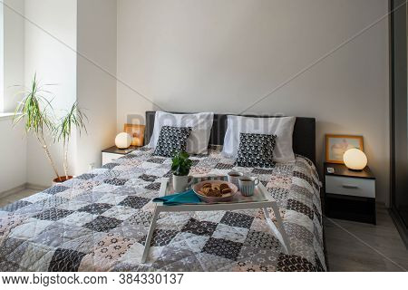 View Of King-size Bed With Tray And Bedsides With Round Lamps In Modern Bedroom. Interior In Light T