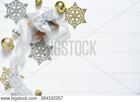 Beautiful Christmas Composition On A White Background With A Gift Box, Silver Ribbon And Christmas B