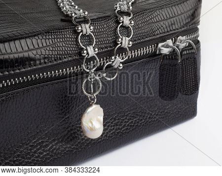 Women`s Silver Chain Necklace With Baroque Pearl Pendant On Female Black Leather Cosmetic Bag. Close