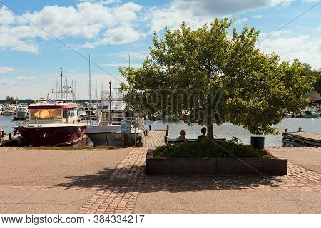 Two Elderly Women Are Sitting In The Shade On A Warm Day At The Harbor Of Kotka, Finland. The Harbor