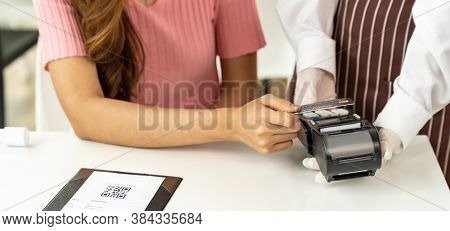 Panoramic Close up Asian woman customer make contactless credit card payment after eating out in new normal social distance restaurant to reduce touching. Online contactless and technology concept.