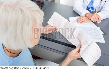 Elderly Patient Looking At The Results Of A Cardiogram Of Her Heart In A Cardiologists Office. Diagn