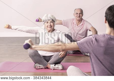 Elderly Man And Woman During Wellness Seniors Workout At Gym
