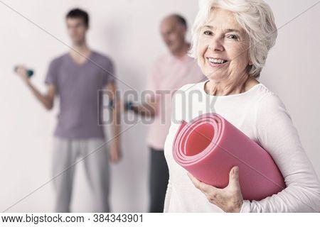 Happy Senior Woman Holding Pink Joga Mat, Men Exercising In Background