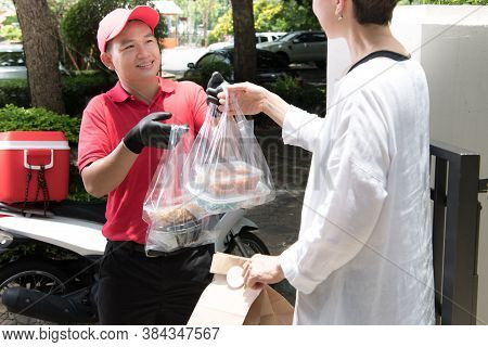 Asian Delivery Man In Red Uniform Delivering Shopping Bags Of Food And Drink To Woman Recipient At H