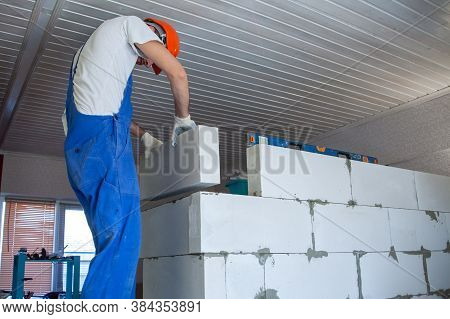Master Foreman Puts A Wall Of Aerated Concrete Blocks When Building A House. Private Housing Constru
