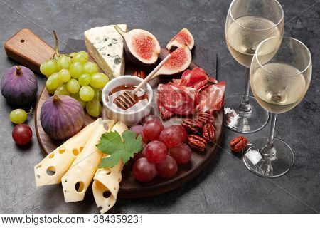 Antipasto plate with prosciutto, cheese, figs and grapes. Appetizer board and white wine