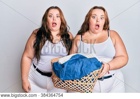 Plus size caucasian sisters woman holding laundry basket afraid and shocked with surprise and amazed expression, fear and excited face.