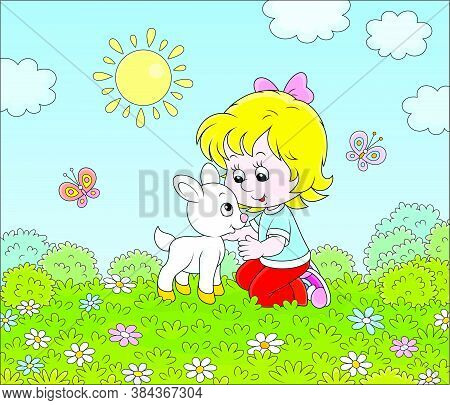 Happy Little Girl Playing With A Small White Kid Among Wildflowers On Green Grass Of A Summer Field