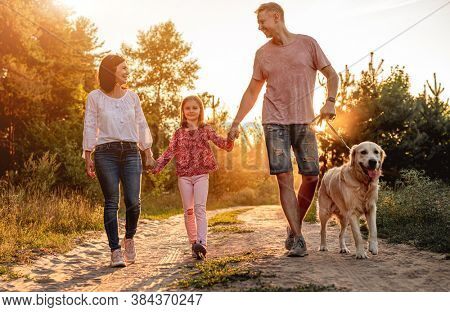 Family with dog walking outdoors at sunset