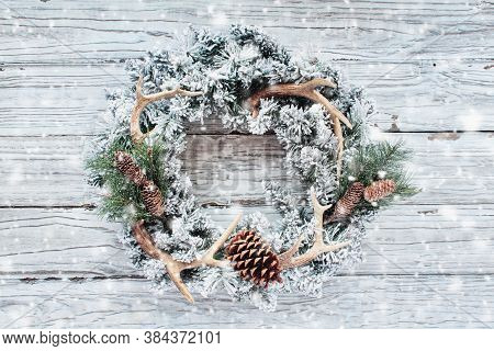 Flocked Country Or Hunters Christmas Wreath Over White Wood Background With Falling Snow. Made With