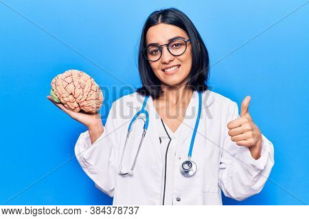 Young beautiful latin woman wearing doctor stethoscope holding brain smiling happy and positive, thumb up doing excellent and approval sign