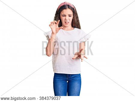 Cute hispanic child girl wearing casual white tshirt disgusted expression, displeased and fearful doing disgust face because aversion reaction.