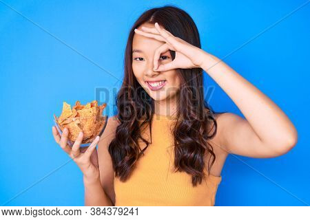 Young beautiful chinese girl holding nachos potato chips smiling happy doing ok sign with hand on eye looking through fingers