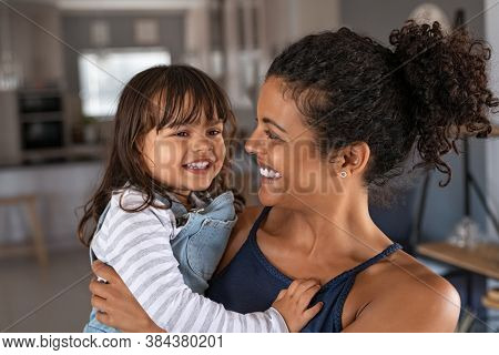 Happy african mother carrying smiling daughter in her arm. Young beautiful woman holding cute little girl in hands. Lovely black mom embracing her child at home.