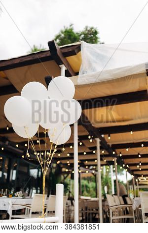 A Bunch Of White Helium Balloons On The Background Of Tables In The Restaurant And Garlands.