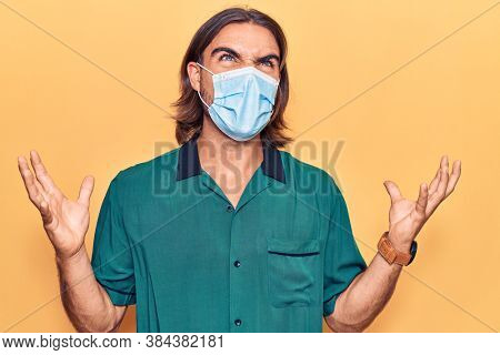 Young handsome man wearing medical mask crazy and mad shouting and yelling with aggressive expression and arms raised. frustration concept.