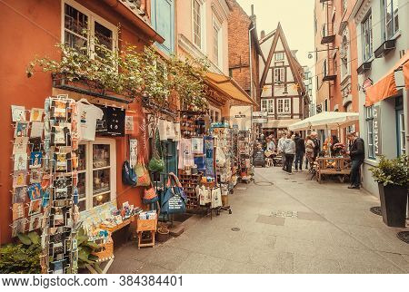 Bremen, Germany: Narrow Streets With Souvenir Stores Of Historical Town And Many Visitors Walking Ar