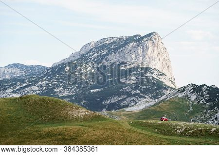 Zabljak, Montenegro - 23 July 2020: Tourists In A Red Car, Camped On The Grass, Against The Backdrop