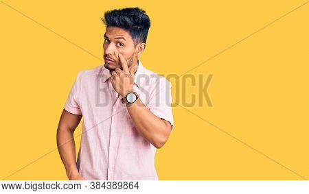 Handsome latin american young man wearing casual summer shirt pointing to the eye watching you gesture, suspicious expression