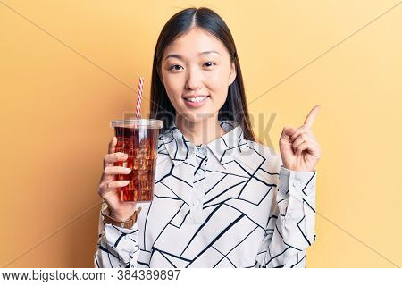 Young beautiful chinese woman drinking cola refreshment beverage smiling happy pointing with hand and finger to the side