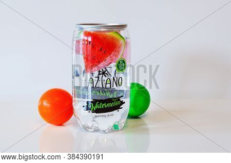 Carbonated Watermelon Drink Aziano In Transparent Tin Can On White Surface. Green And Red Balls Are