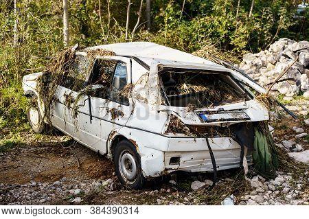 Zabljak, Montenegro - 23 July 2020: Flood Damaged Car. A Dented White Passenger Car, Broken Windows,