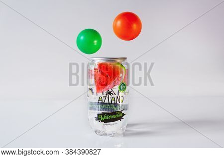 Carbonated Watermelon Drink Aziano In Transparent Tin Can On White Surface. Green And Red Balls Levi