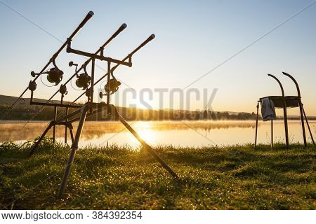 Carp Fishing Rods With Carp Bite Indicators And Reels Set Up On Rod Pod Near Lake River. Fishing Dur