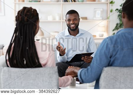 Psychological Help For Couples. Friendly Black Family Counselor Talking To Spouses During Therapy Se