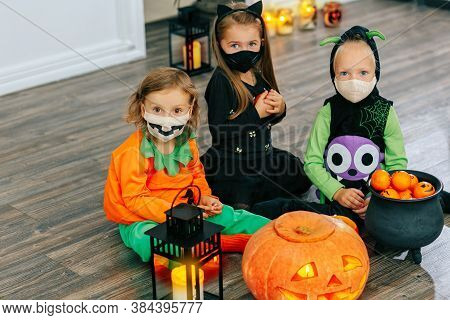 Kids In Carnival Costumes Celebrate Halloween In Face Masks And Play With Pumpkins And Candy Indoors