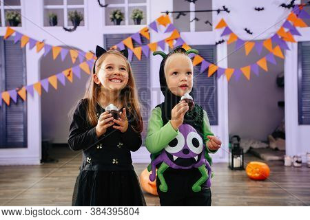 Children's Trick Or Treat In A Halloween Costume And Face Masks Eat Treats And Have Fun Laughing. Ki