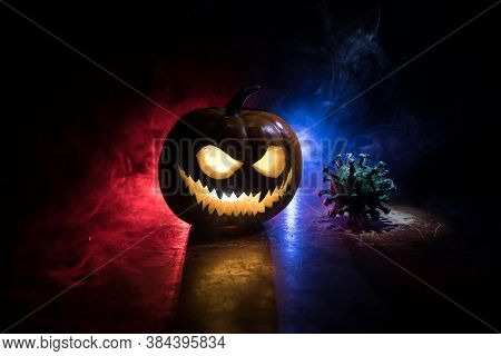 Halloween During Corona Virus Global Pandemic Concept. Glowing Pumpkins And Covid Novel On Dark With