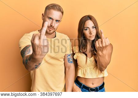 Young couple of girlfriend and boyfriend hugging and standing together showing middle finger, impolite and rude fuck off expression