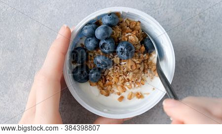 Eating Yogurt With Granola And Blueberries. Female Hands Holding Bowl Of Greek Yogurt With Berries A