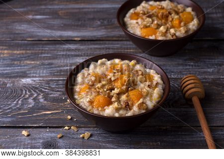 Delicious Oatmeal Porridge With Baked Pumpkin, Honey And Nuts In Ceramic Bowl On Wooden Table. Healt