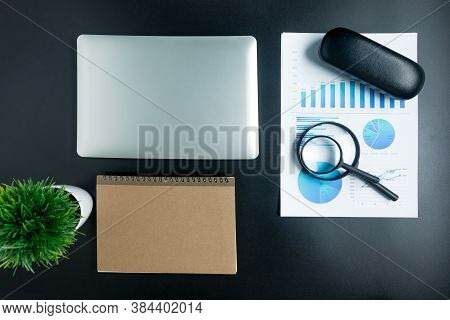 Top View, Black Desk With Computer Graph, Magnifier And Calculator Of Businessmen In The Office.