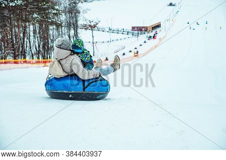 Parent With Kid Sliding Down By Snowed Hill With Snowing Tube