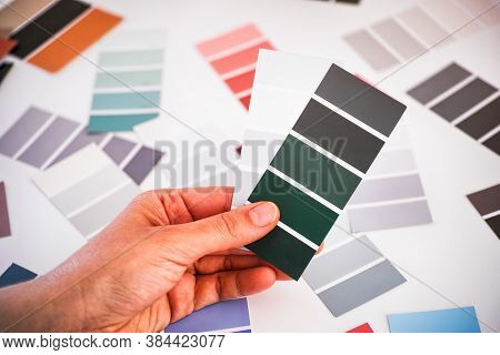 Woman Hand Choosing Green And Gray Sample Palettes. Close-up.