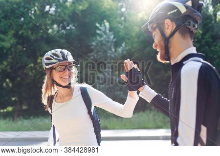 Man And Woman In Protective Bicycle Helmets Give Each Other High Five After Successful Sport Trainin