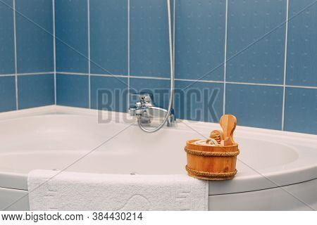 Wooden Ladle With A Brush, Washcloth And Other Shower Accessories On The Rim Of A Corner Bathtub Nea