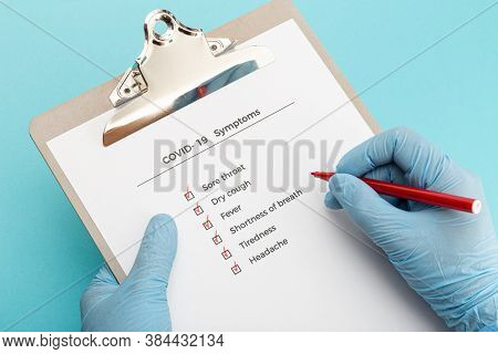 Hands Wearing Protectives Gloves Holding A Checklist On Clipboard With Covid-19 Symptoms
