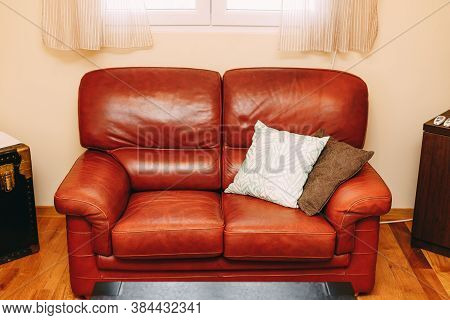 Folding Sofa Made Of Burgundy Genuine Leather With White And Brown Pillows Under The Window With Bei