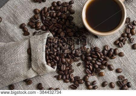 Coffee Scattered From A Linen Bag And A Cup Of Black Coffee Espresso Or Americano Standing On A Wood