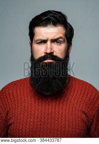 Confident Man Has Beard And Mustache, Looks Seriously, Isolated. Hipster Serious Guy Thinking With E