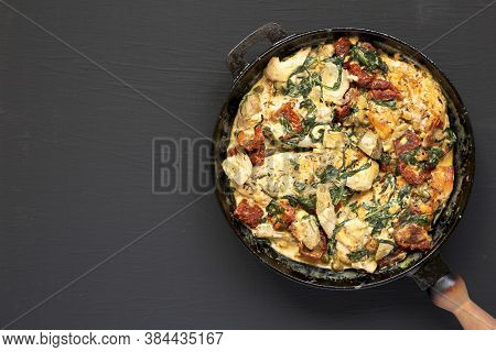 Homemade Creamy Tuscan Chicken In A Cast-iron Pan On Black Background, Top View. Flat Lay, Overhead,