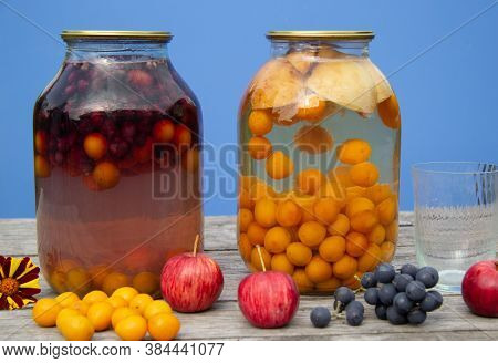 Two-litre Cans With Compote Stand On A Wooden Surface. There's A Blue Wall In The Back. Homemade Har