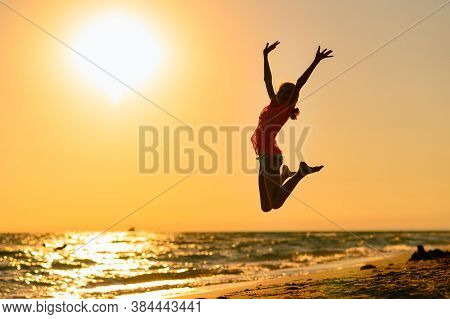 Happy Girl Jumping On The Beach Against The Background Of The Sea And Sunset. Sunset At Sea. Girl Ju